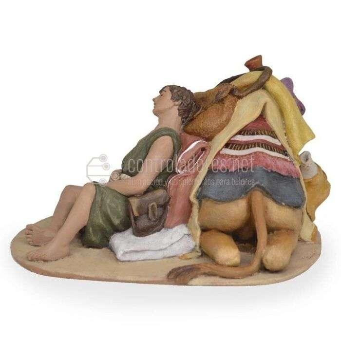 Camello tumbado con pastor descansando